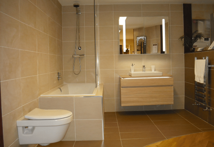 Designer bathroom with floating units and tiled walls and bath.